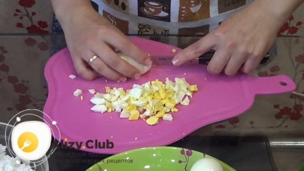 Для приготовления пирожков с рисом и яйцом в духовке, нарежьте яйца.
