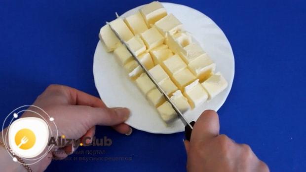 Для приготовления бананового пирога на кефире, нарежьте масло.