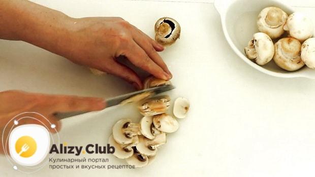 По рецепту, для приготовления пиццы с шампиньонами нарежьте грибы.