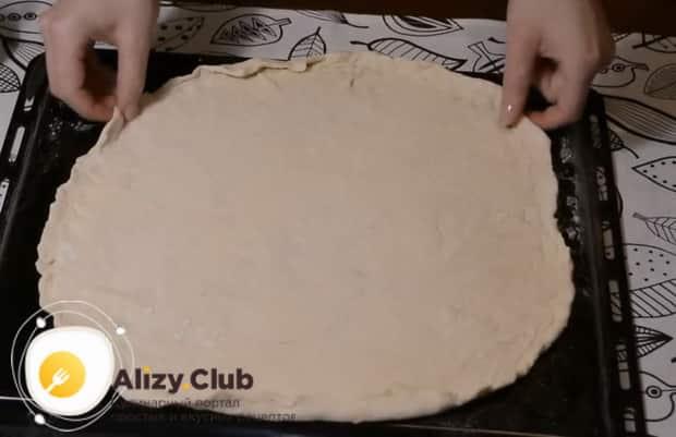 Для приготовления пиццы с фаршем выложите тесто на противень.