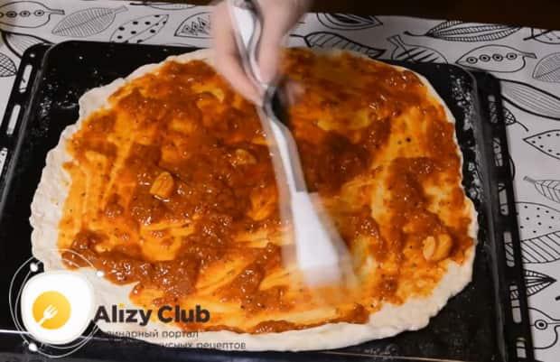 Для приготовления пиццы с фаршем смажьте тесто соусом.
