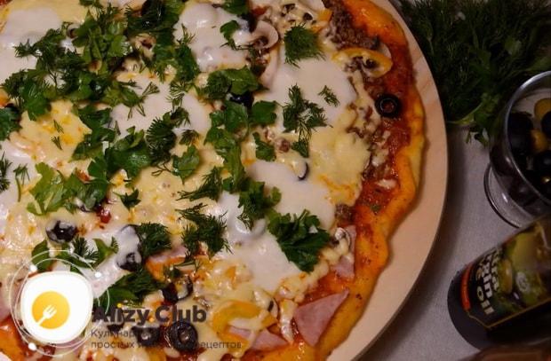 Посыпьте пиццу с фаршем зеленью.
