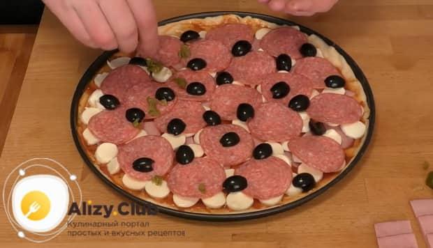 Для приготовления пиццы папперони выкладываем на колбасу маслины.