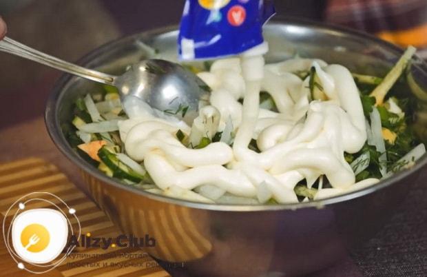 Для приготовления салата с редькой и огурцом заправьте салат майонезом.