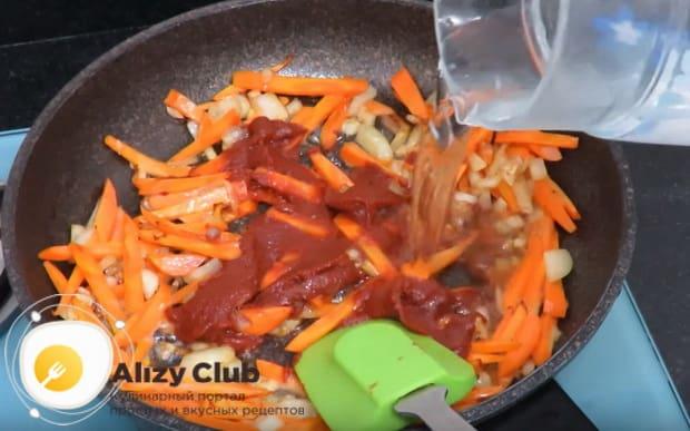 добавляем томатную пасту и заливаем водой