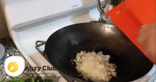 Для приготовления курицы в тыкве запеченной в духовке, обжарьте лук.