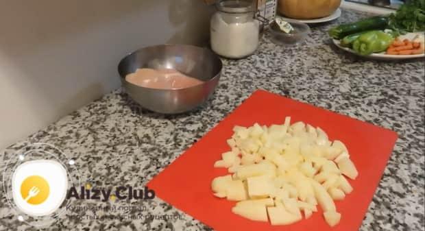 Для приготовления курицы в тыкве запеченной в духовке, нарежьте картофель.