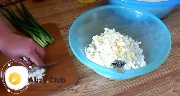 Для приготовления жареных пирожков с рисом и яйцом, нарежьте лук.