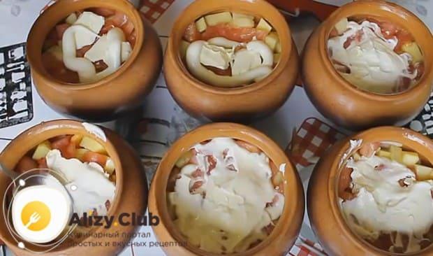 Покрываем содержимое каждого горшочка ложкой майонеза.