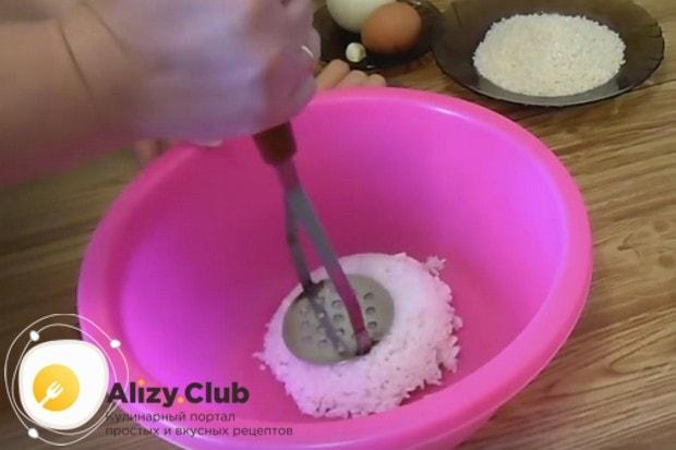 Почти остывший рис перекладываем в миску и разминаем толкушкой.