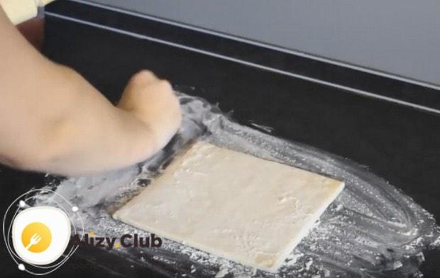 На присыпанный мукой стол выкладываем размороженное готовое слоеное тесто.
