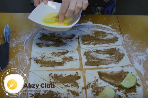 Каждую дольку яблока обмакиваем в масло и кладем на тесто.