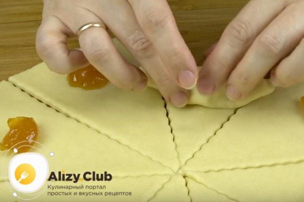 Кладем на треугольнички начинку и заворачиваем, формируя рогалики.