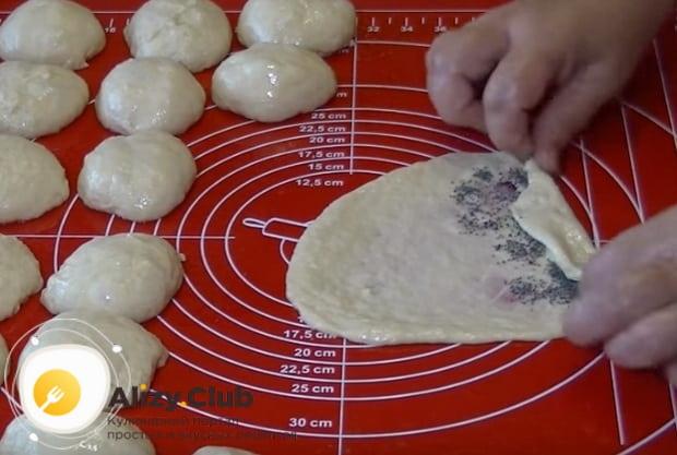 Выкладываем на треугольники маковую начинку и формируем рогалики