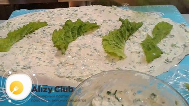 Поверх соуса разложите 40 г листьев салата