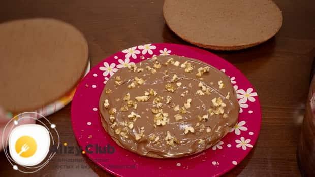 Смажьте коржи шоколадного торта на кипятке в мультиварке кремом и присыпьте орехами.