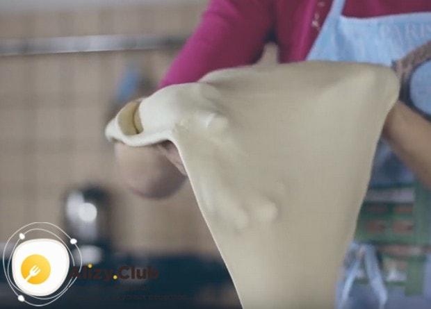 Для приготовления штруделя раскатываем тесто как можно тоньше и немного растягиваем его руками.