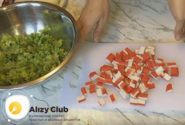 нарзае кусочками крабовые палочки и отправляем в миску в листьям салата.