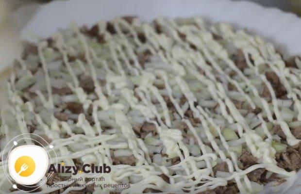 На мясо кладем слой маринованного лука и поливаем майонезом.