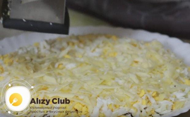 Яйца покрываем слой натертого на терке твердого сыра.