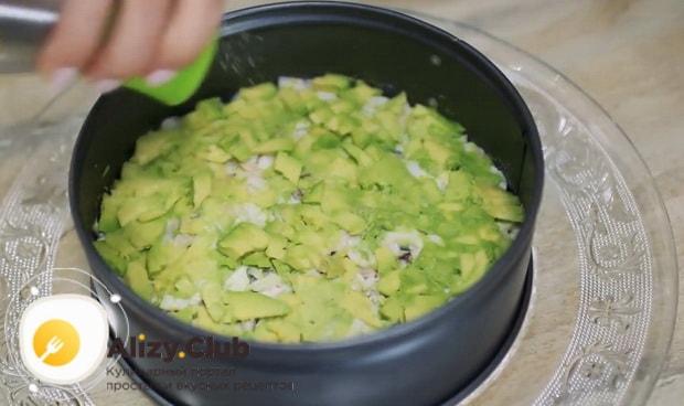 Выложите слой авокадо для приготовления салата нежность