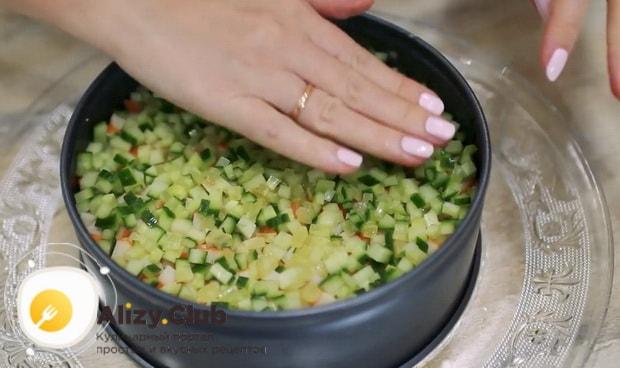 Выложите слой огурцов для приготовления салата нежность