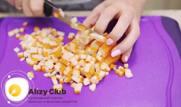 Нарежьте крабовые палочки для приготовления салата нежность