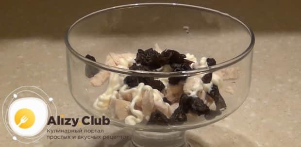Выложите слой чернослива для приготовления салата нежность