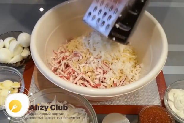 На крупной терке прямо в салатницу трем твердый сыр и яичные белки.