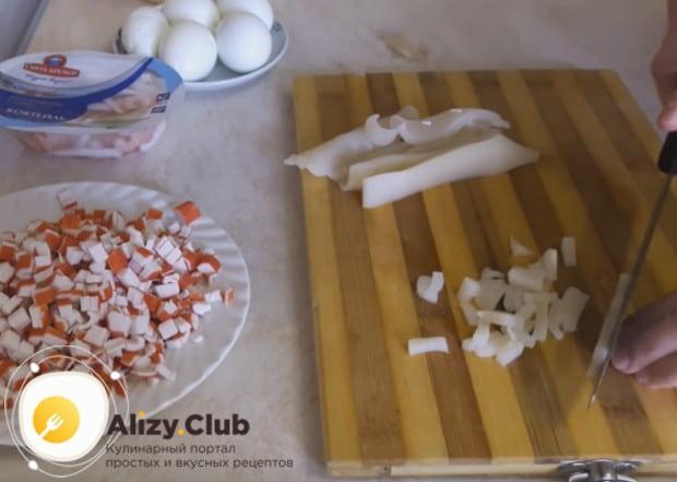 Так же, кубиком, режем отваренную тушку кальмара.