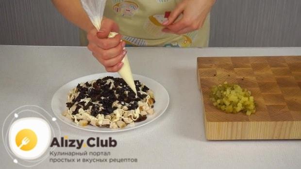 Наносим сеточку из майонеза и выкладываем слой нарезанного чернослива