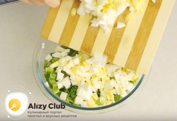 Выкладываем нарезанные яйца в миску к черемше.