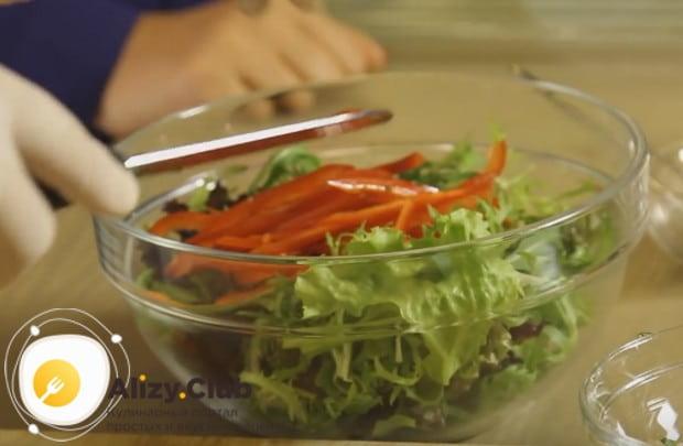 Выкладываем в салатницу листья салата и болгарский перец.