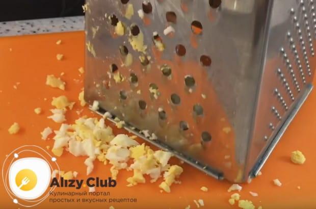 На крупной терке трем отваренные вкрутую яйца.