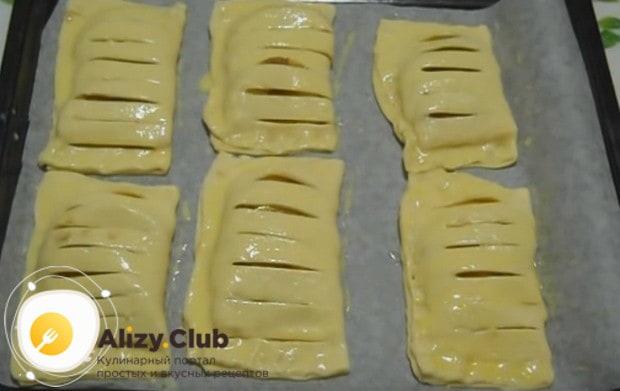 Смазываем наши сладкие пирожки из слоеного теста смесью желтка и молока и украшаем их небольшими надрезами.