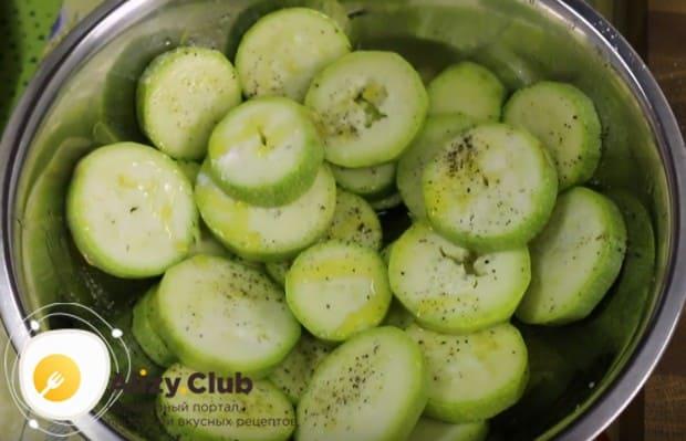 Нарезанный кружочками кабачок и баклажан маринуем солью, перцем и оливковым маслом.