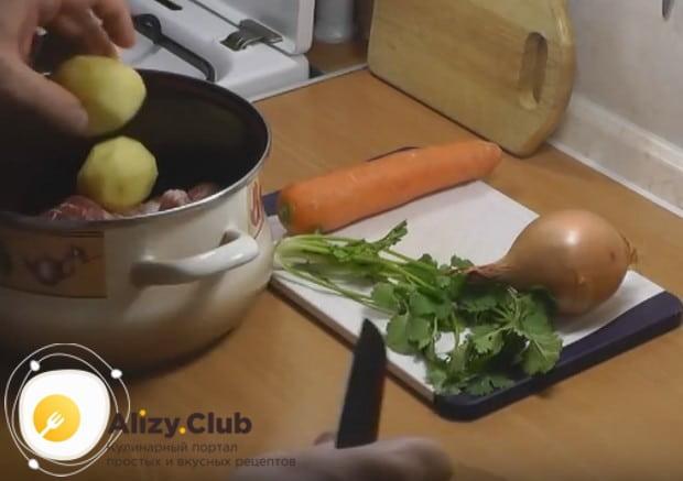 Очищаем и кладем в кастрюлю к баранине целую картошку.