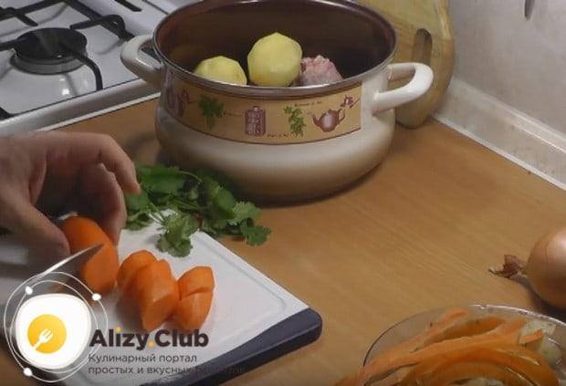 Морковь режем крупными кружочками и тоже кладем в кастрюлю.