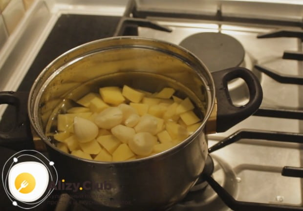 Чтобы приготовить вкусный крем-суп из кабачков и картофеля, очищаем картошку, режем на кусочки и ставим вариться вместе с головкой чеснока.