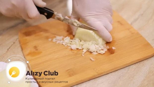 Для приготовления супа с фрикадельками и рисом нарежьте лук.