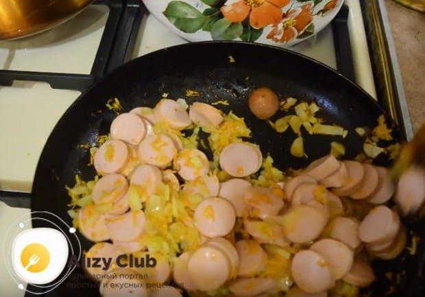Выкладываем к овощам сосиски и обжариваем вместе.