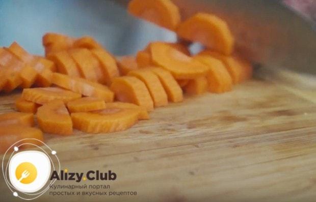 Чтобы приготовить сырный суп с грибами в мультиварке, полукольцами нарежем морковку.