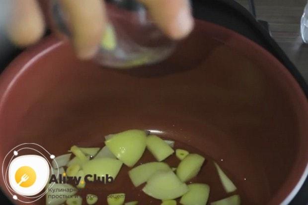 В чашу мультиварки наливаем растительное масло и выкладываем лук с чесноком.