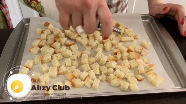 Обжарьте сухарики для приготовления салата из куриной печени с грибами