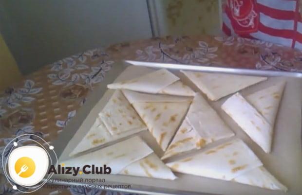 Кладем треугольники из лаваша с творогом кладем на застеленный пергаментом противень.