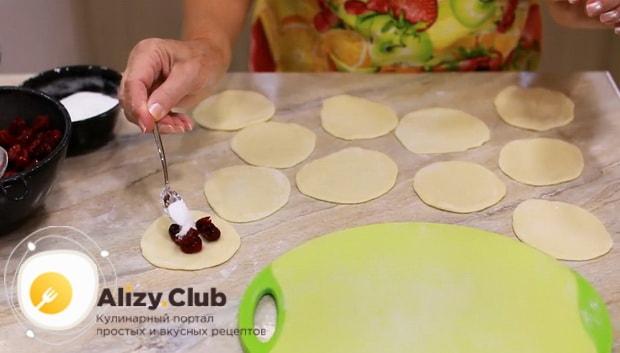 Положите начинку на тесто для приготовления вареников с вишней.