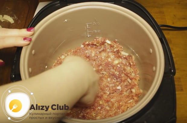 Чашу мультиварки смазываем растительным маслом и выкладываем половину фарша.