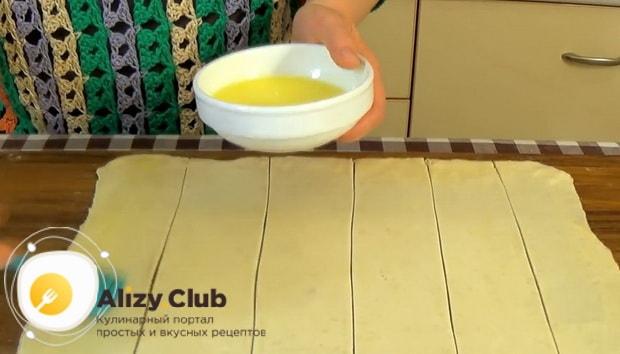 Для приготовления булочек из слоеного теста с яблоками смажьте тесто яйцом.