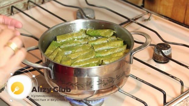 По рецепту, для приготовления долмы в виноградных листьях, поставьте кастрюлю на огонь.