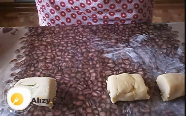 Для приготовления торта на сковороде со сгущенкой разрежьте тесто на кусочки.